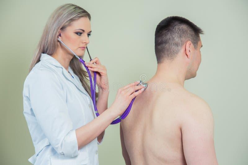 医院:医师检查患者与听诊器 库存图片