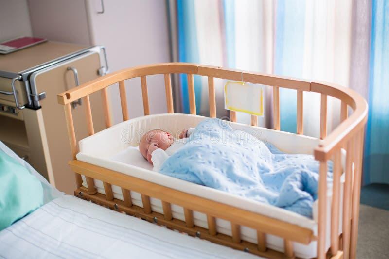医院轻便小床的新出生的男婴 免版税库存图片