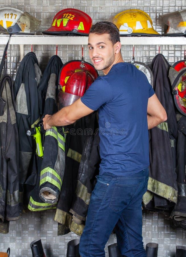 去除制服的微笑的工作者垂悬在消防局 库存图片
