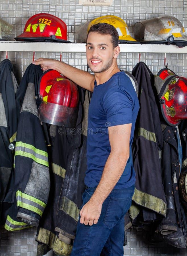 去除制服的消防员垂悬在消防局 免版税库存照片