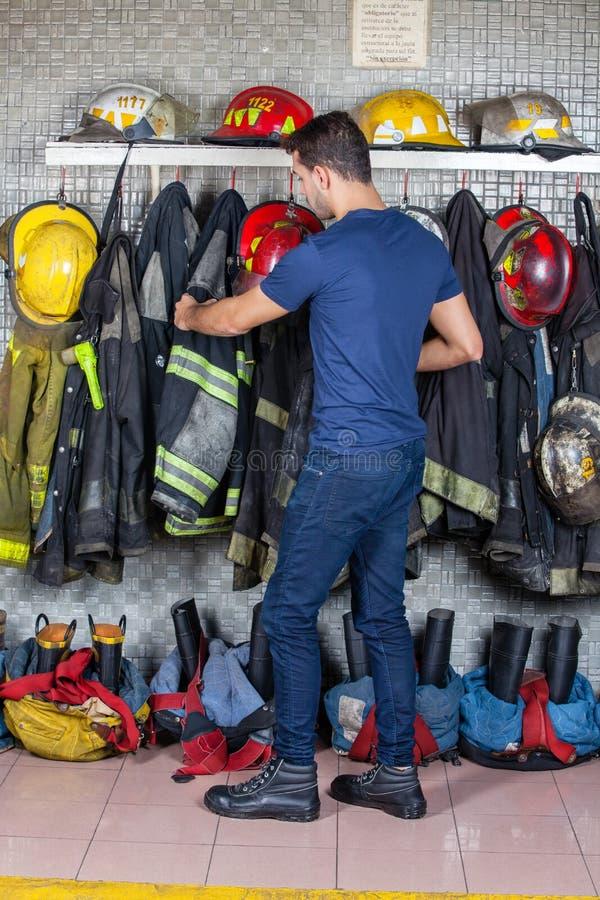去除制服的消防队员垂悬在火 库存图片
