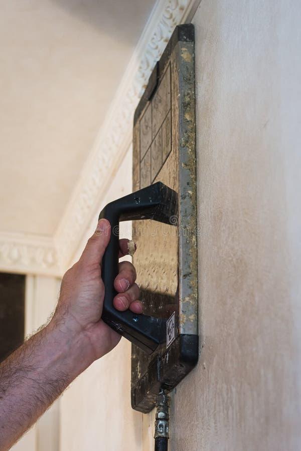 去除墙壁的老墙纸通过使用蒸汽设备 免版税库存照片