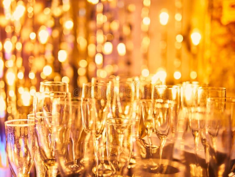 除夕与杯的庆祝背景香槟 葡萄酒金烟花和bokeh在除夕和拷贝空间 A 免版税库存图片