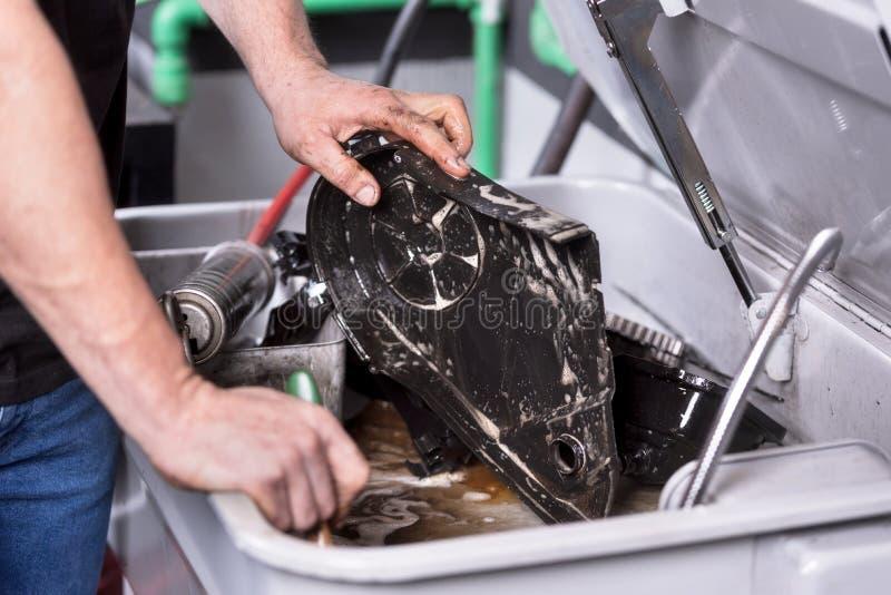 除油发动机零件的技工在服务修理驻地 免版税图库摄影