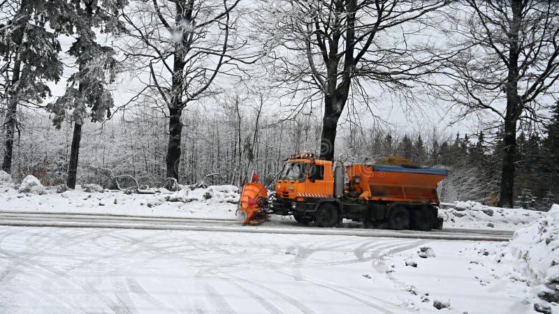 除雪机服务卡车-在路的铺砂机汽车传播的盐看法  路维护在山的冬天 库存照片