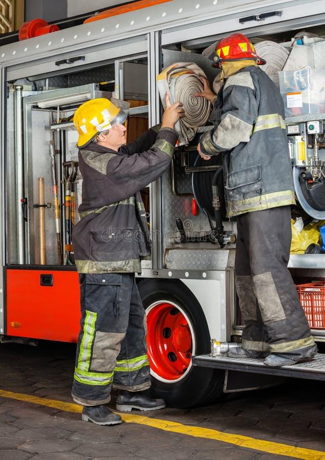 去除水管的消防队员从卡车 库存图片
