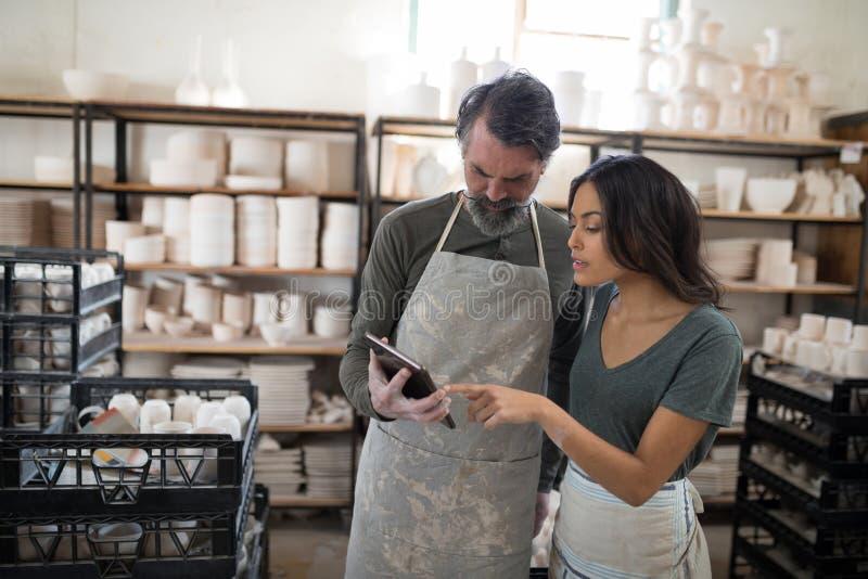 陶瓷工同事谈话在片剂 免版税库存照片