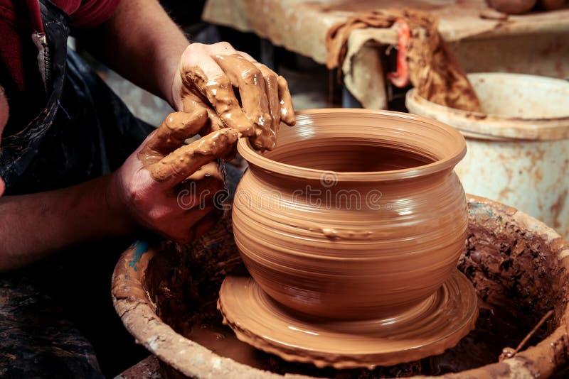陶瓷工在工作 车间 陶瓷工的现有量,创建在圈子的一个土制瓶子 免版税库存照片