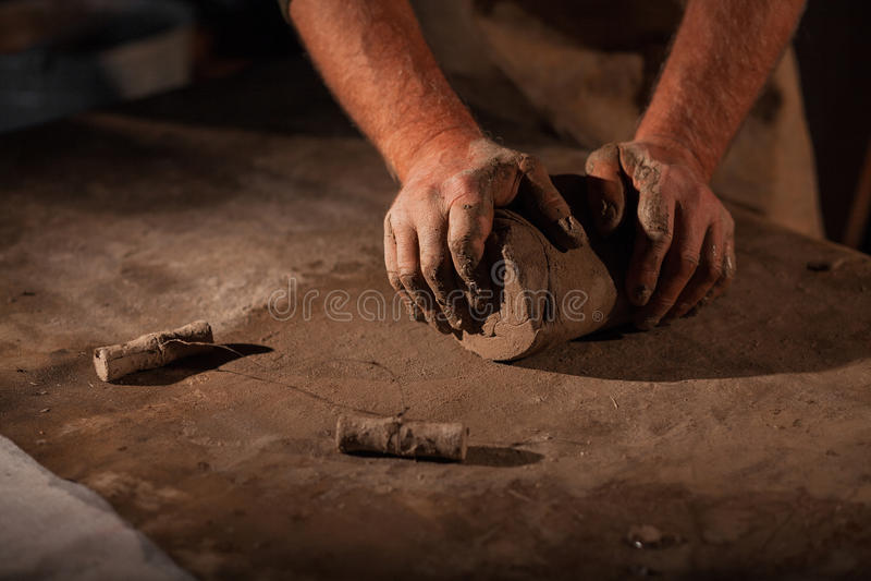 陶瓷工的手揉黏土 免版税库存图片