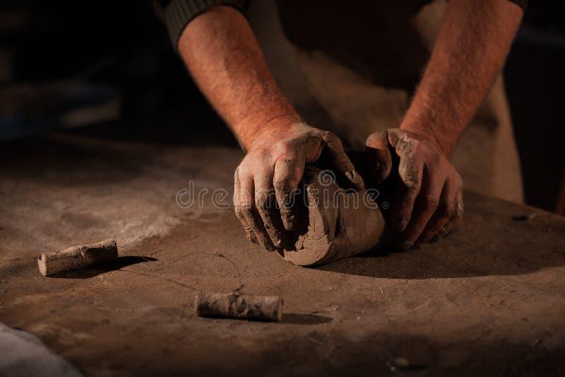 陶瓷工的手揉黏土 免版税库存照片