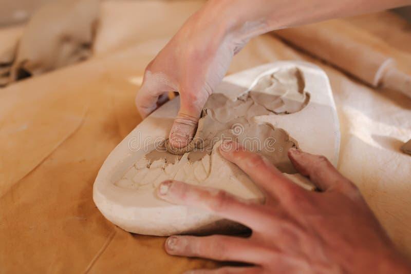 陶瓷工的手用陶瓷填装形式以蝴蝶的形式 关闭手 图库摄影