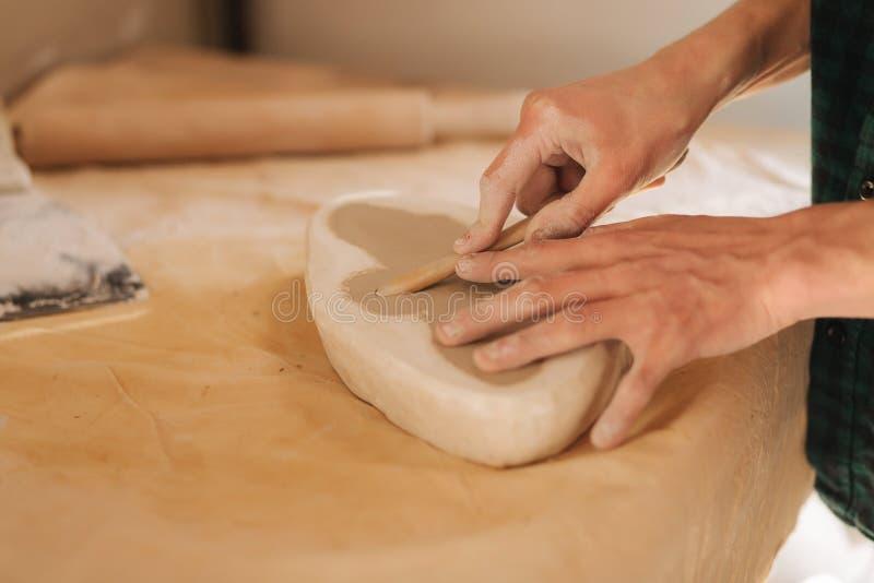 陶瓷工的手用陶瓷填装形式以蝴蝶的形式 关闭手 免版税库存照片