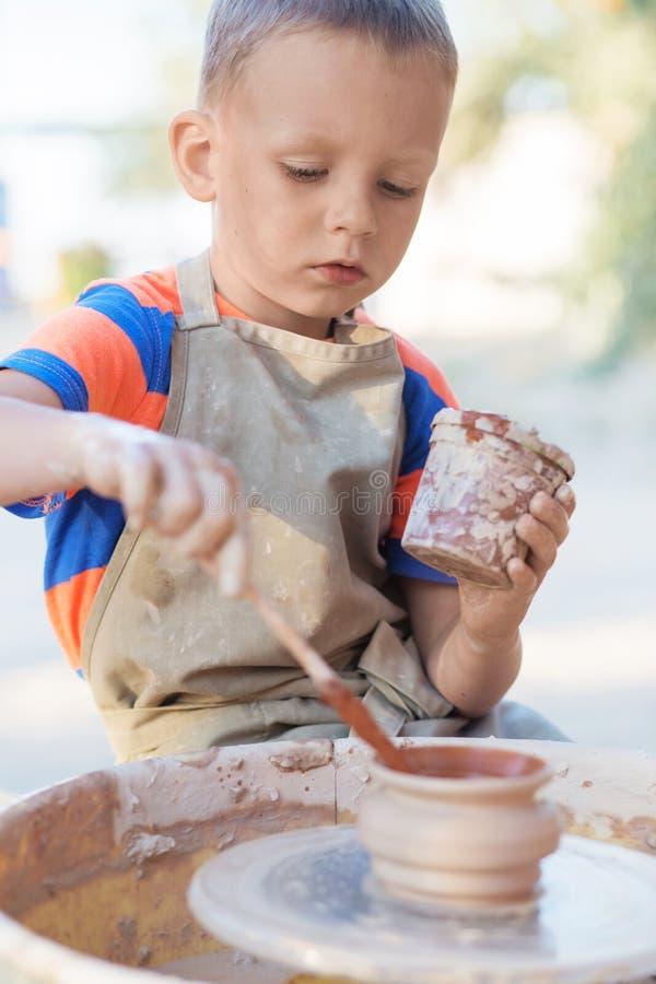 年轻陶瓷工的手,创造在圈子的一个土制瓶子,分类 图库摄影