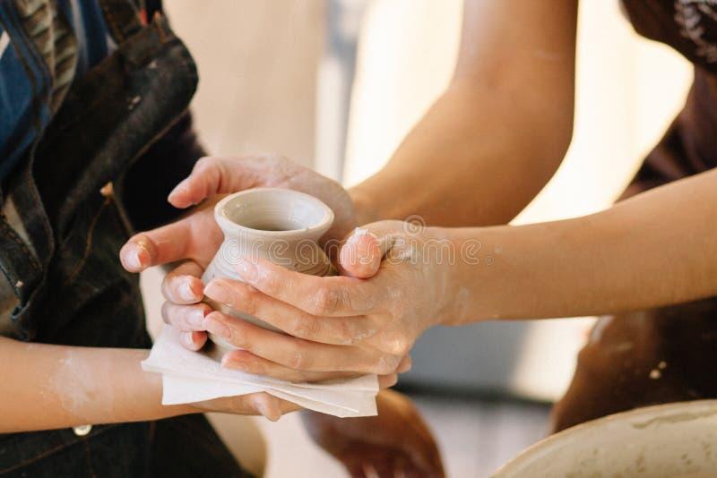 陶瓷工的老师在孩子的手投入一个罐黏土,在车间期间,他接受 库存照片