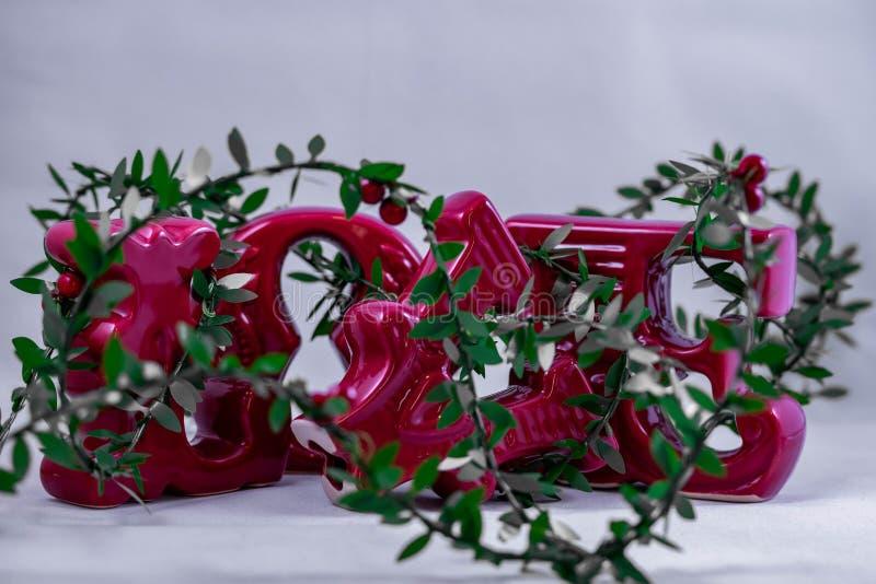 陶瓷情书装饰与在白色背景显示的圣诞节闪亮金属片 免版税图库摄影