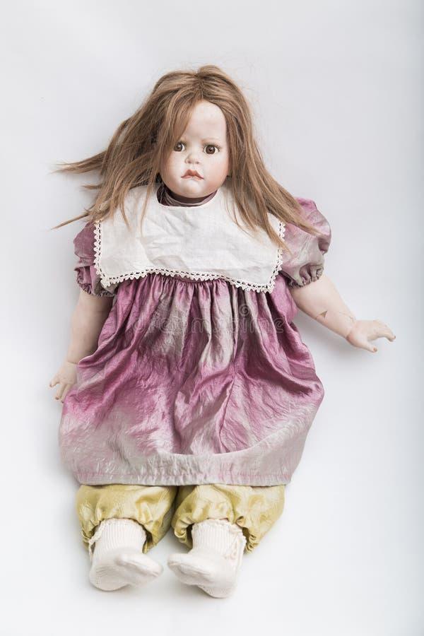 陶瓷有金发的瓷手工制造玩偶和紫罗兰穿戴 免版税图库摄影