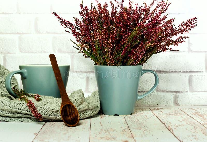 陶瓷杯子和木匙子在白色木背景与石南花,hugge样式,拷贝空间 库存图片