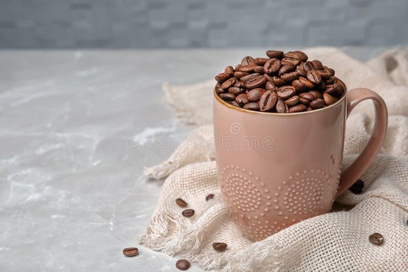 陶瓷杯子用咖啡豆 免版税图库摄影