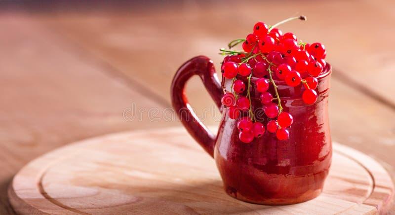陶瓷杯子用在一个木背景土气样式的新鲜的红浆果 库存照片