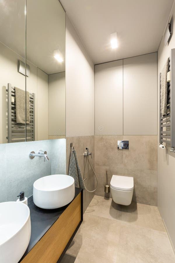 陶瓷水盆和洗手间在一现代,花梢卫生间interi 免版税库存图片