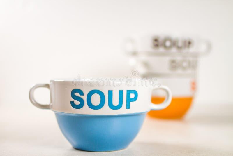 陶瓷汤碗用在他们的词汤蓝色在前面 免版税库存图片