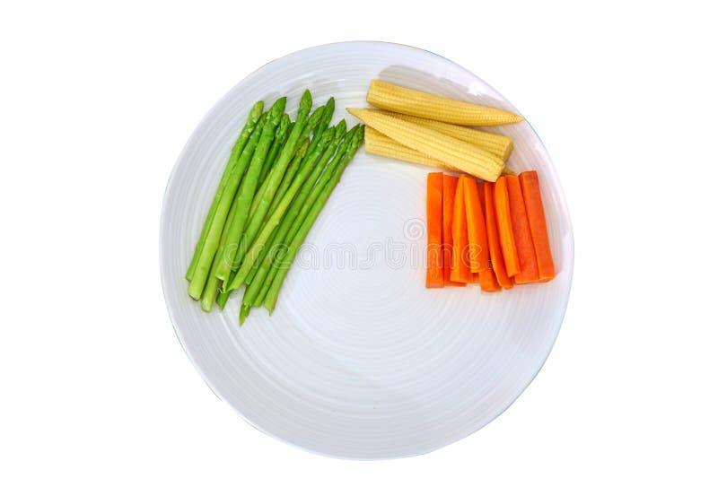 陶瓷牛排板材用切的红萝卜,油煎的芦笋,煮沸 免版税库存图片