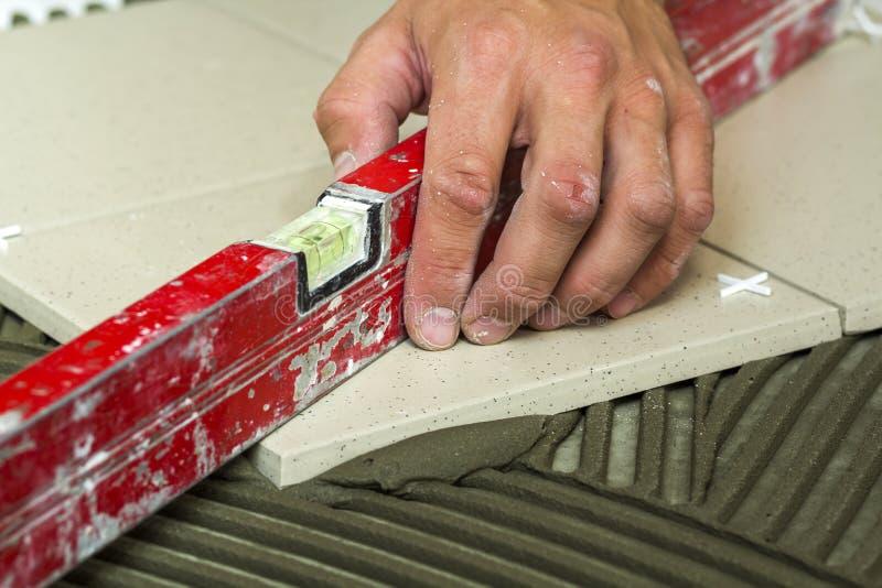 陶瓷砖和工具为铺磁砖工 安装地垫的工作者手 住所改善,整修-陶瓷砖地板胶粘剂, 免版税图库摄影