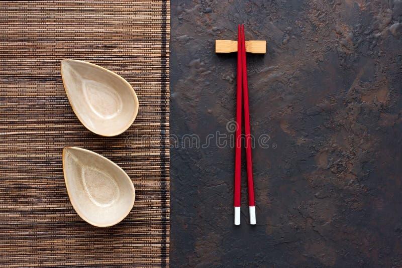 陶瓷碗顶视图有筷子的在dar的竹席子 免版税库存照片