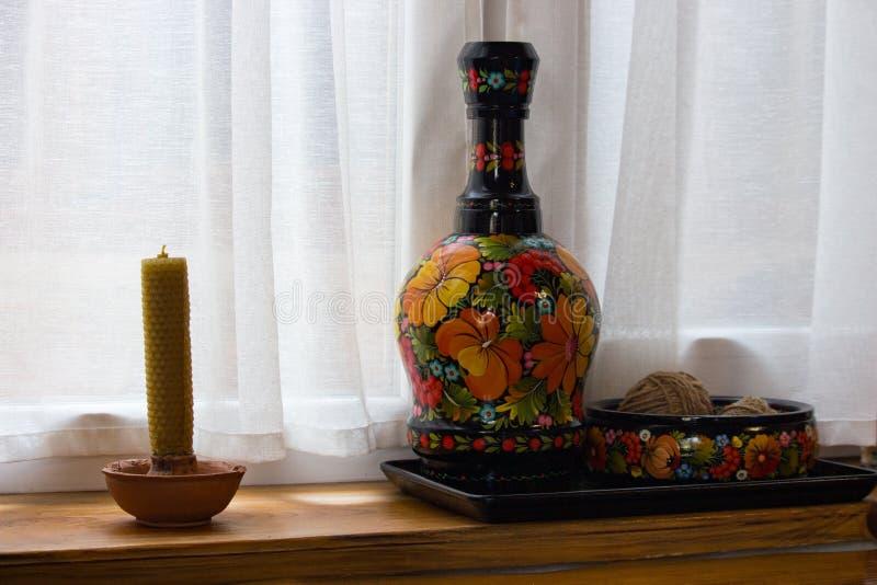 陶瓷被绘的花瓶和罐和蜡烛在窗台 传统乌克兰手工制造装饰 种族土气纪念品 免版税库存照片