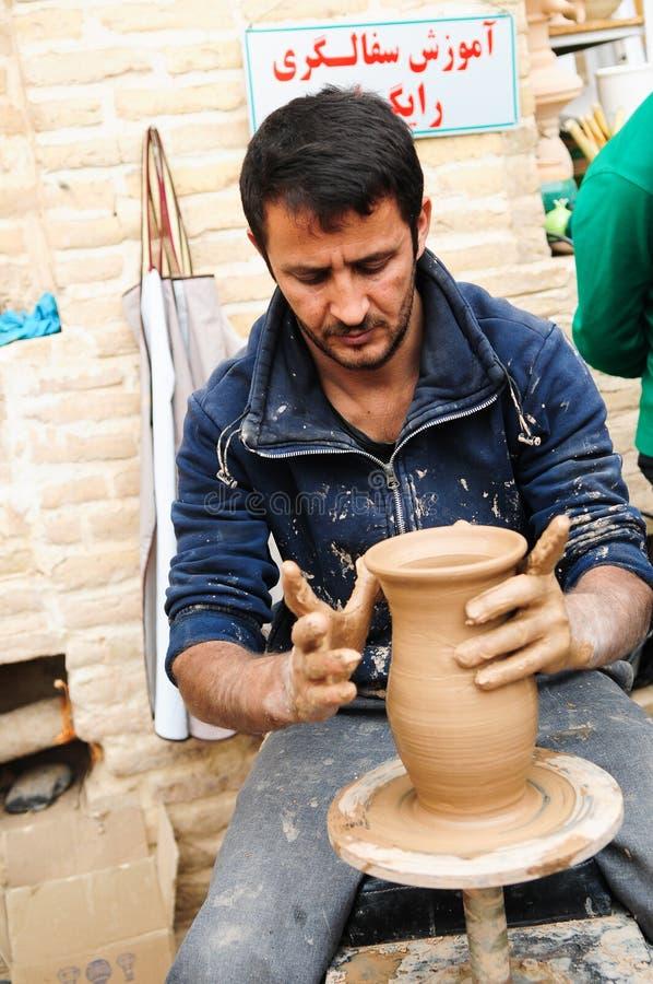 陶轮上制作陶壶的街道艺术家 免版税库存照片