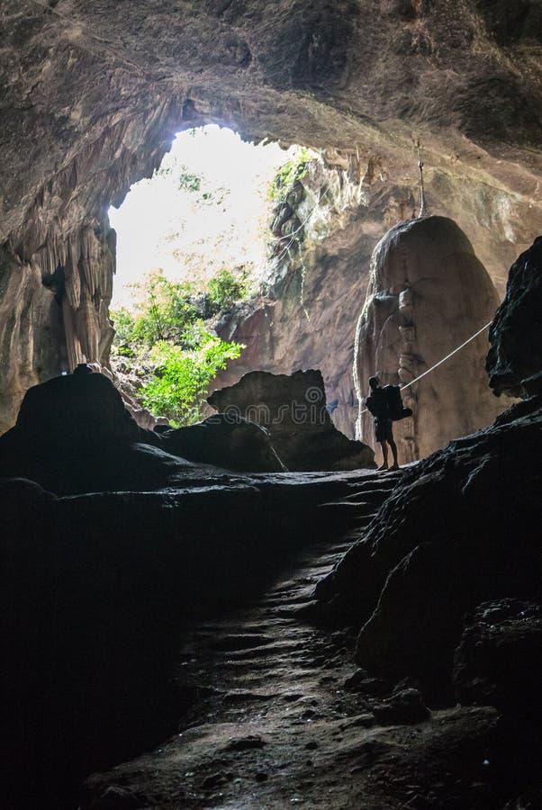 陷下与站立在入口前面的一个岩石的人 库存图片