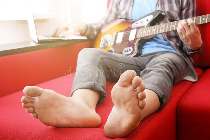 随便有在家演奏歌曲的吉他的加工好的年轻人在屋子里 网上吉他教训概念 男性吉他弹奏者实践 免版税库存图片