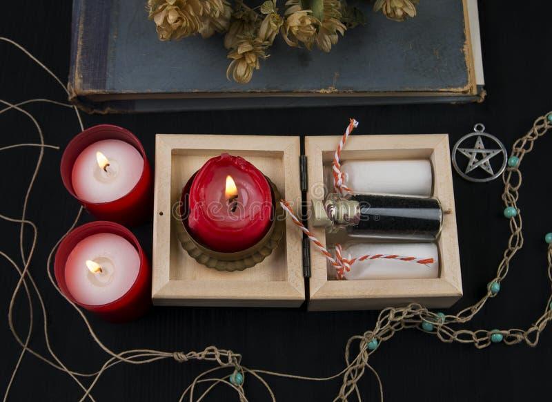 隐密法坛用蛇麻草、蜡烛和魔药 免版税图库摄影