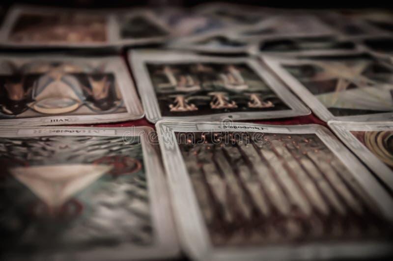 隐密神秘的tarot甲板和老放置在不可思议的异教的通灵命运读书的桌的占卜用的纸牌特写镜头  库存照片