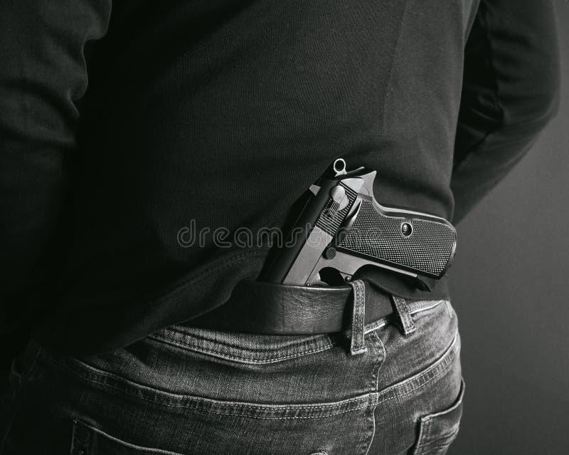 隐瞒他的在他的后的匪徒枪  后面和白色照片 免版税库存图片