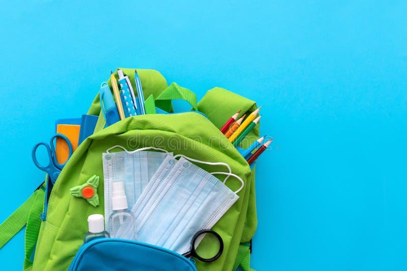 隔离概念后重返学校 具有学校用品和一组消毒剂和医用防护面具的背包 免版税图库摄影