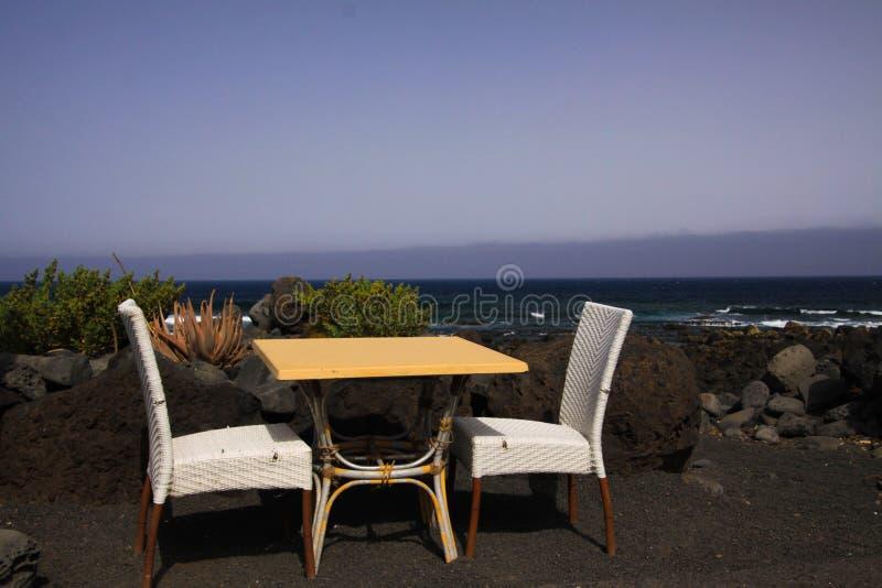 隔绝了两张白色椅子和桌在黑熔岩沙滩有海洋和波浪背景- El Golfo,兰萨罗特岛 免版税库存图片