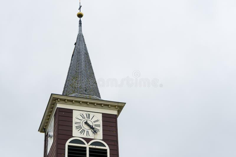 隔绝在romal数字的白色天空教会钟楼 老看的村庄小钟楼 点屋顶和金黄球 免版税库存图片