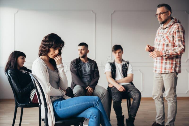 隔绝的沮丧的妇女从她的精神疗法小组在精神病院 免版税库存图片