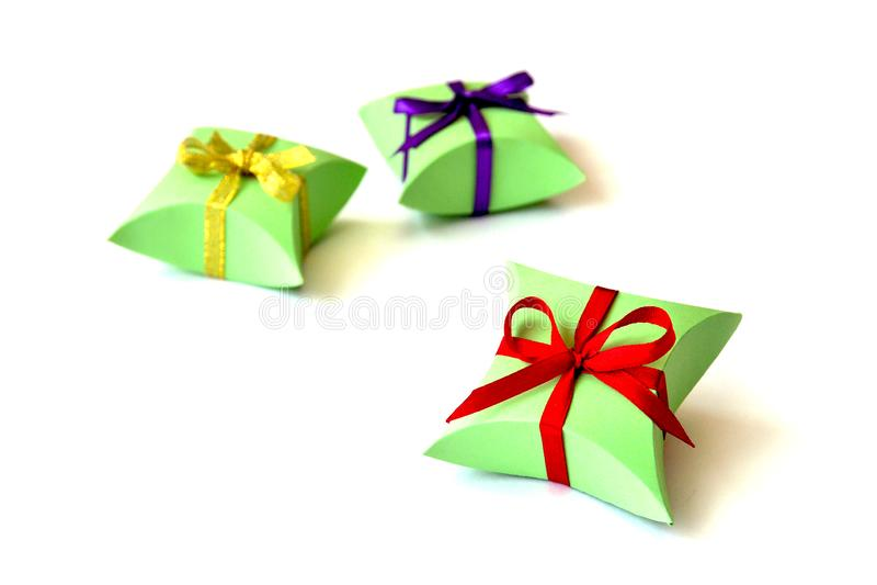 隔绝首饰的三个苹果绿的纸礼物盒与在白色背景的红色,紫罗兰色,金黄缎带弓 库存照片
