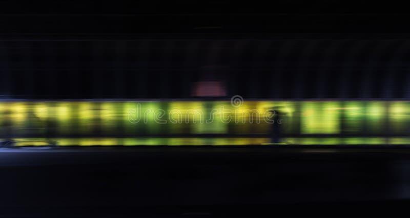 隧道的步行者在霓虹色的墙壁前面 免版税库存图片