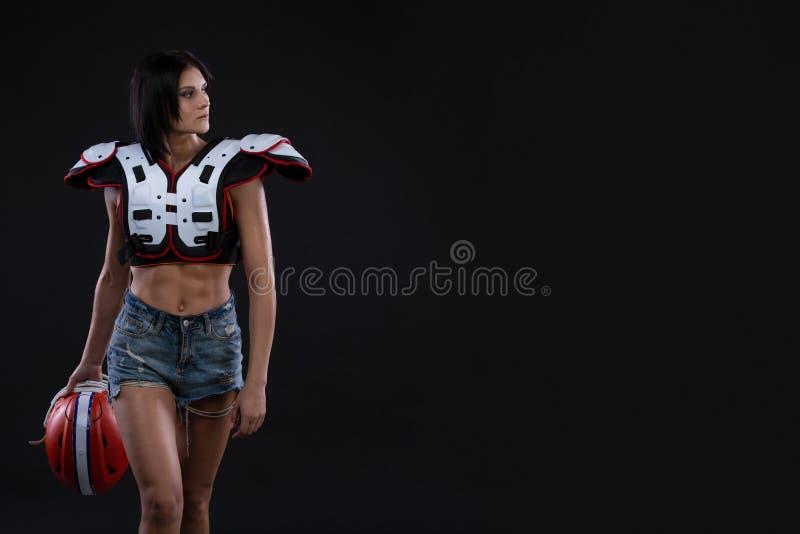 难以置信地的美丽,运动深色的女孩shoulderpads和展示惊人的惊人的吸收的一件橄榄球盔甲 免版税库存图片