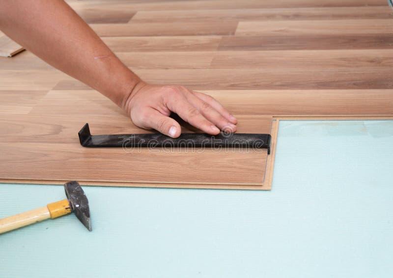难倒安装层压制品 安装新的层压制品的木地板的人 安装与锤子的工作者木层压制品的地板 免版税库存照片