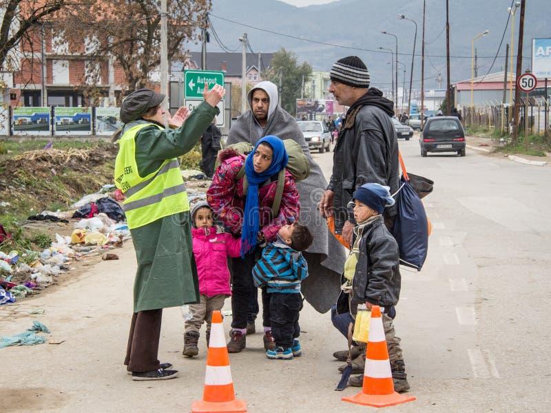 难民家庭谈论与在他们的途中的一个NGO志愿者登记和进入塞尔维亚在与马其顿的边界 库存图片