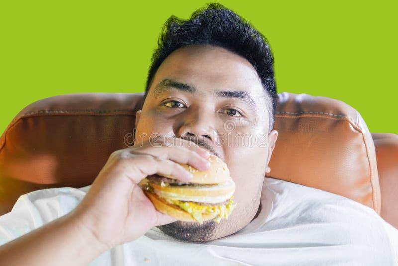 难满足肥胖食人在沙发的一个汉堡 库存图片