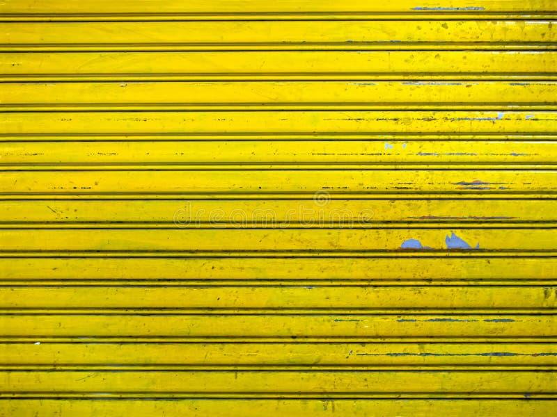 难看的东西明亮的黄色路辗快门门纹理背景 免版税库存图片