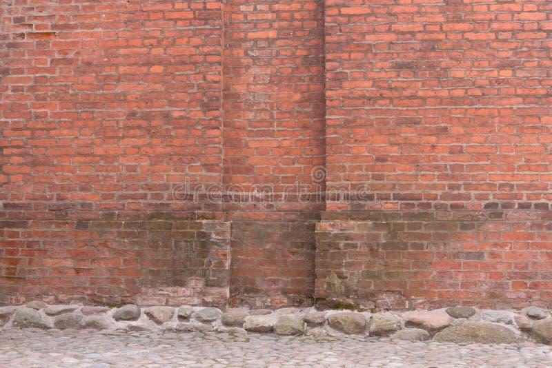 难看的东西红砖墙壁和石头路面 都市的背景 库存图片