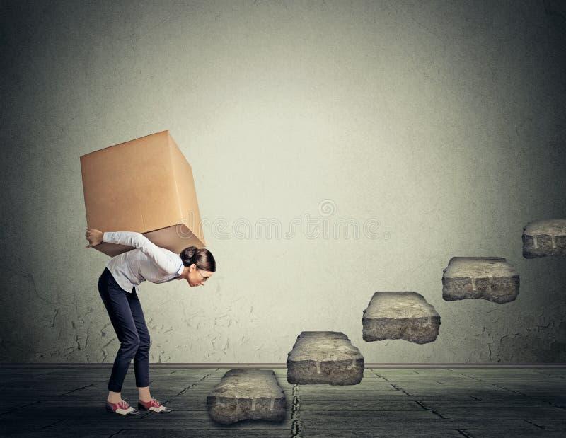 难题概念 运载重的箱子的妇女在楼上 库存照片