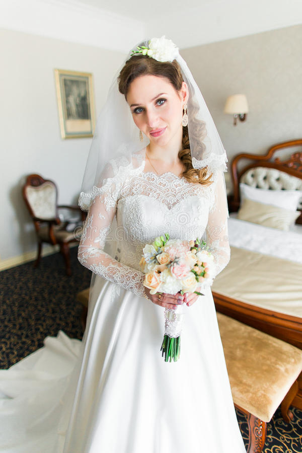 难以置信地美丽,年轻新娘摆在一件壮观的礼服的旅馆客房的和精美花束 库存图片