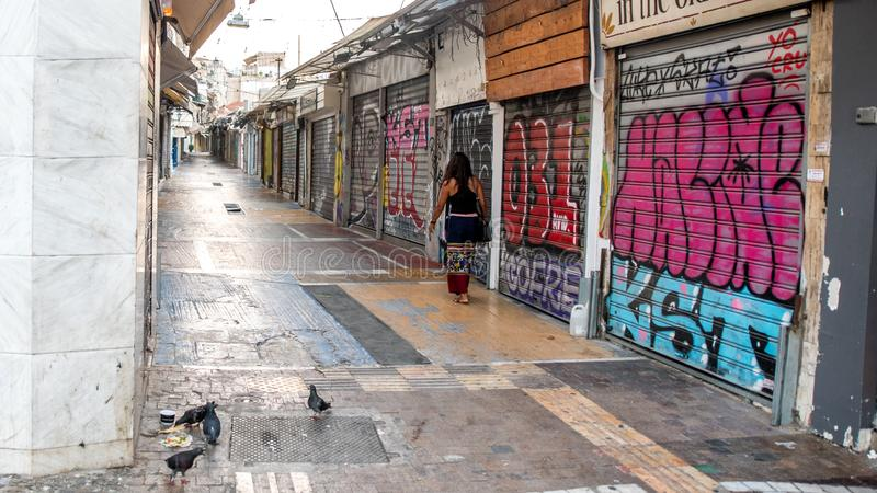 雅典希腊/2018年8月17日:步行沿着向下被关闭的fl的妇女 库存图片